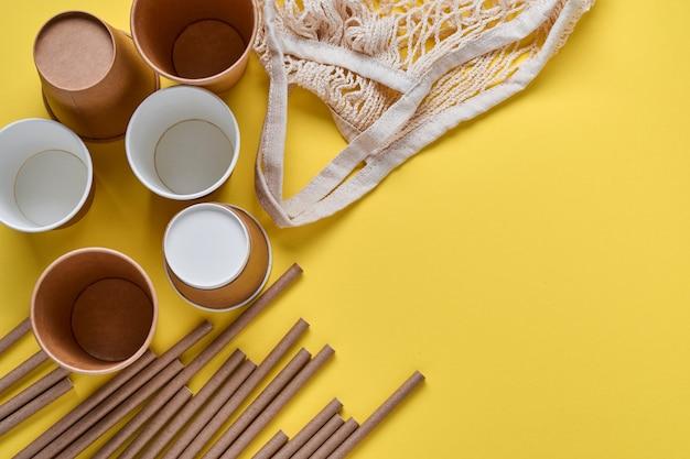 Bruine buizen rietjes gemaakt van papier en maizena, mesh markttas en lege papieren koffiekopjes op een trendy grijze en gele achtergrond. geen afval en plasticvrij concept. bovenaanzicht.