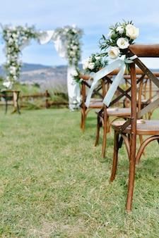 Bruine chiavari stoelen versierd met witte eustomas op het gras en de versierde trouwboog op de achtergrond
