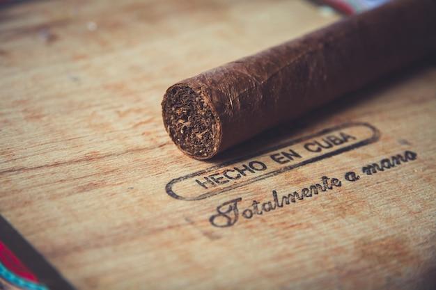 Bruine cubaanse sigaar op vintage houten kist met inscriptie in het spaans: met de hand gemaakt in cuba