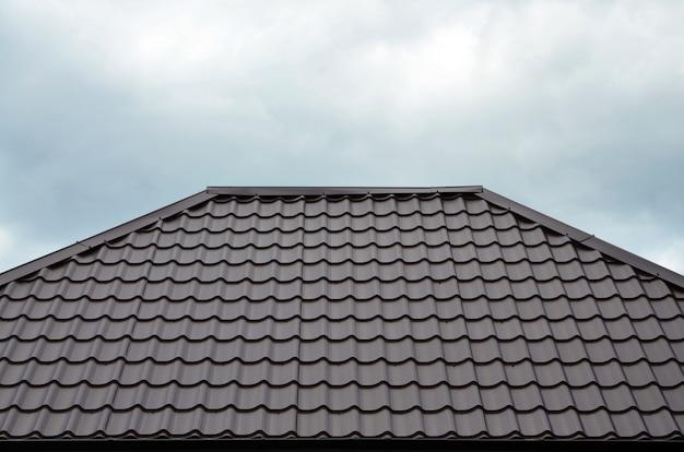 Bruine daktegels of dakspanen op huis als achtergrond. nieuw overlappend bruin klassiek dakwerkmateriaaltextuurpatroon op een echt huis