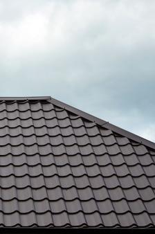 Bruine daktegels of dakspanen op huis als achtergrond