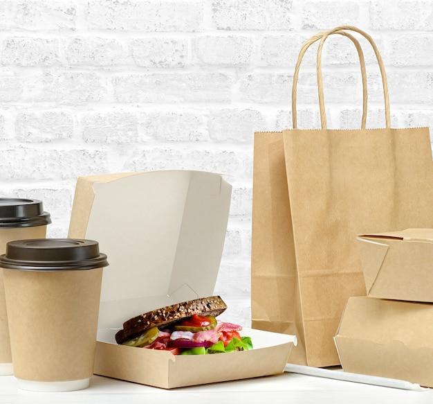 Bruine doos met sandwich. fastfood verpakking. papieren koffiekopjes, bruine papieren zak op tafel op witte bakstenen muurachtergrond