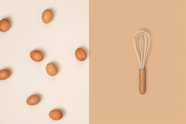 Bruine eieren en zwaai met houten handvat op beige achtergrond. plat lag bovenaanzicht concept.