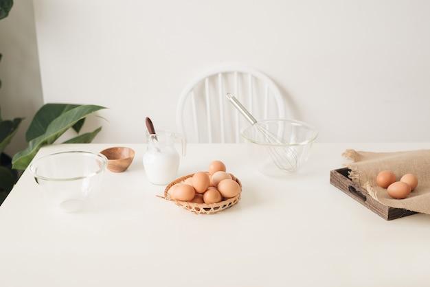 Bruine eieren in een rieten mand op een lichte houten tafel en een zijaanzicht