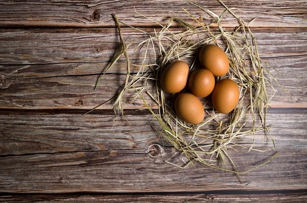 Bruine eieren met stro op een houten ondergrond