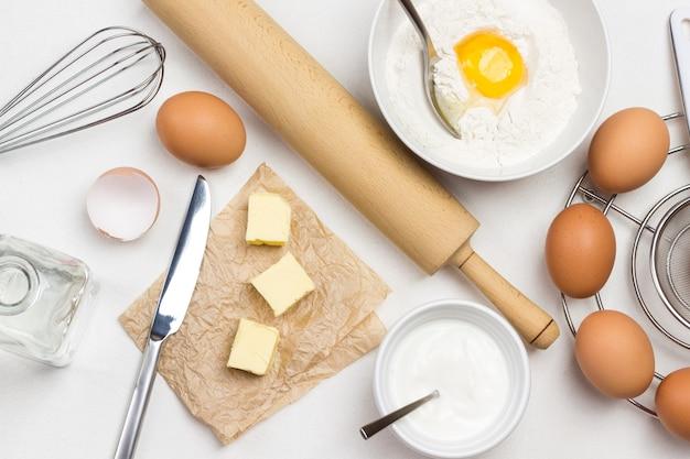 Bruine eieren op metalen standaard. boter en mes op papier. eidooier met bloem en lepel in kom. melk in kom en deegroller op tafel. witte achtergrond. plat leggen