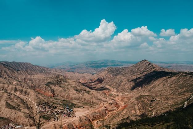 Bruine en grijze bergen onder blauwe hemel overdag