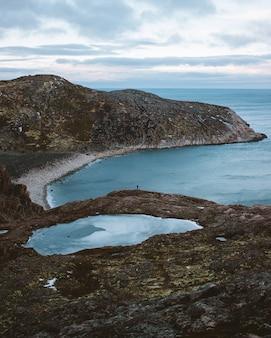 Bruine en groene berg naast watermassa overdag