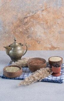 Bruine en groene droge anijszaadjes in houten kopjes.