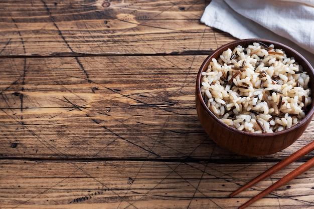 Bruine en ongepelde rijst op een bord met stokjes.