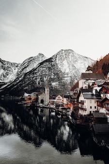 Bruine en witte betonnen huizen dichtbij watermassa en berg
