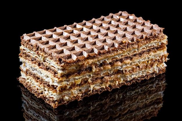 Bruine en witte bladerdeegwafelcake met gekookte gecondenseerde melk die op zwarte achtergrond met bezinning over glanzend oppervlak wordt geïsoleerd