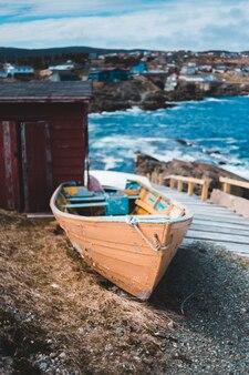 Bruine en witte boot aan kust overdag