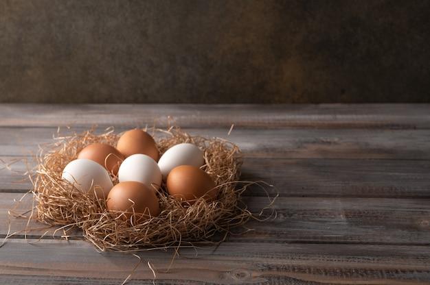 Bruine en witte kippeneieren in een stro-nest op houten achtergrond. rustieke stijl. kopieer ruimte