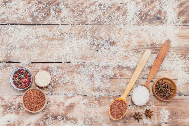 Bruine en witte rijst met droge kruiden op gestructureerde achtergrond