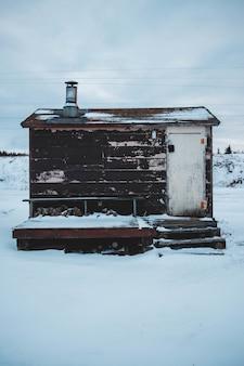 Bruine en witte schuur bedekt met sneeuw