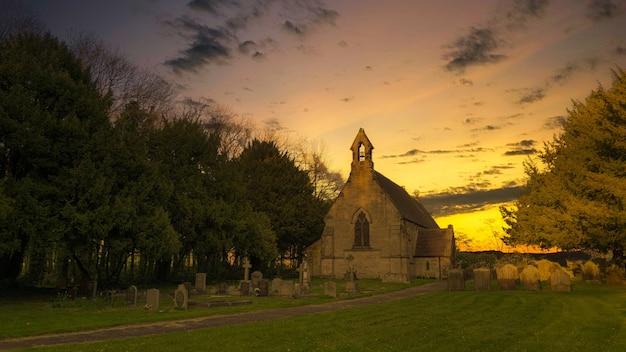 Bruine en zwarte betonnen kerk onder bewolkte hemel overdag