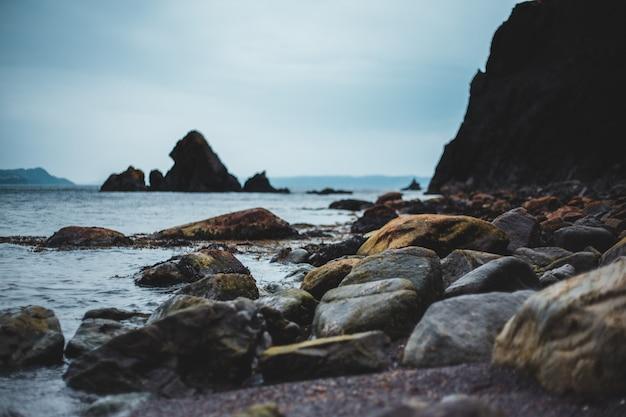 Bruine en zwarte rotsen op de kust overdag