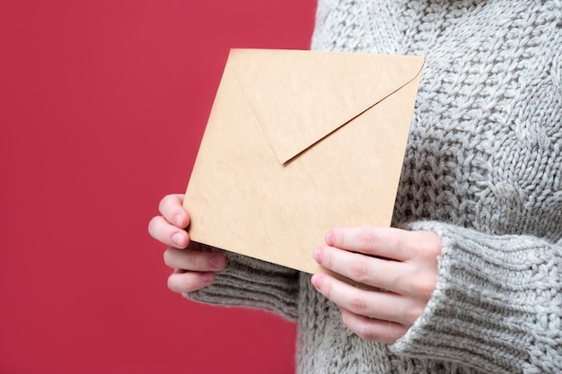 Bruine envelop gemaakt van kraftpapier in vrouwenhanden op een rode achtergrond, close-up. een brief aan de kerstman, verlanglijstje concept. het meisje houdt een brief vast. nieuwjaar achtergrond.