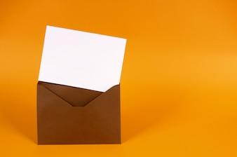 Bruine envelop met blanco uitnodigingskaart