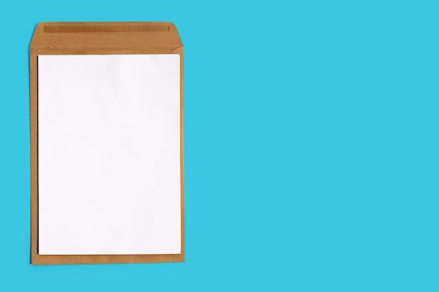 Bruine envelop met wit papier op blauwe achtergrond. kopieer ruimte