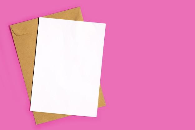 Bruine envelop met wit papier op roze achtergrond. kopieer ruimte