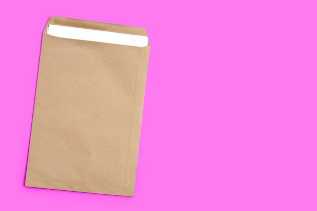 Bruine envelop met wit papier op roze