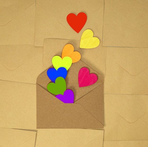 Bruine envelop van kraftpapier met verschillende regenboogkleurige harten op effen bruin