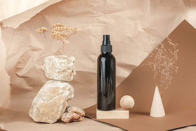 Bruine fles cosmetische producten op steen, houten geometrische vormen op beige papieren achtergrond. natuurlijke biologische spa cosmetische schoonheid concept vooraanzicht.