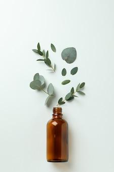 Bruine fles en eucalyptusbladeren op witte achtergrond