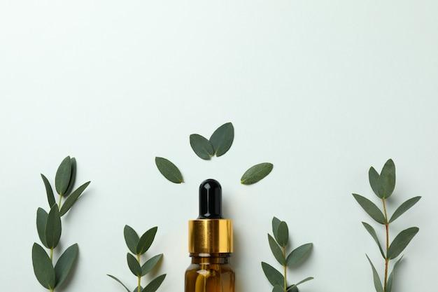 Bruine fles eucalyptusolie en twijgen op witte achtergrond