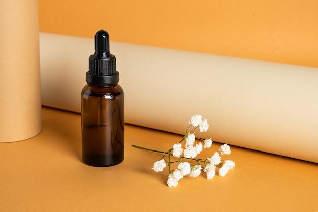 Bruine fles met cosmetische vloeistof op oranje oppervlak