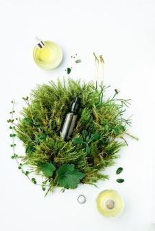Bruine fles met natuurlijk serum, tinctuur, olie op biologische achtergrond van planten