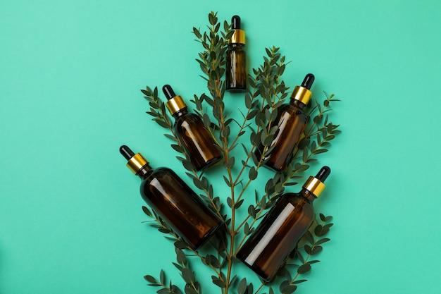 Bruine flessen eucalyptusolie en tak op muntachtergrond