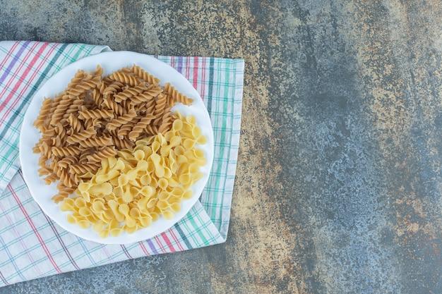 Bruine fusilli pasta en farfalle pasta's in de kom op de handdoek, op het marmeren oppervlak.