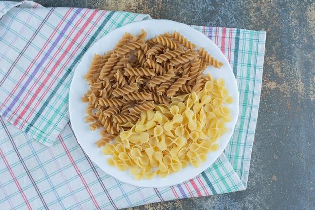 Bruine fusilli pasta en farfalledeegwaren in de kom op de handdoek, op de marmeren achtergrond.