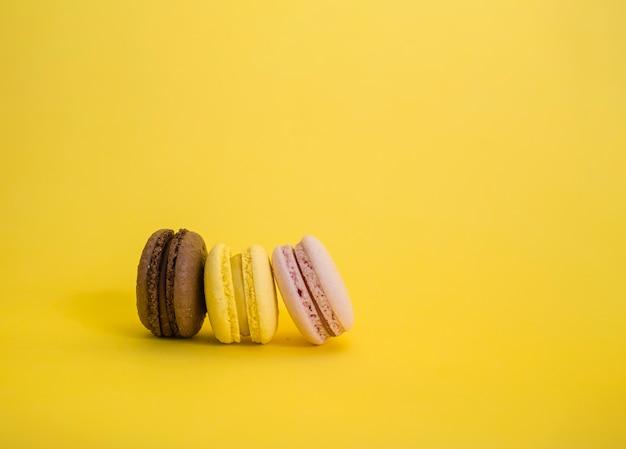 Bruine, gele en roze macaroni staan zijwaarts op een rij. set van drie macarons op een gele ruimte met kopie ruimte.