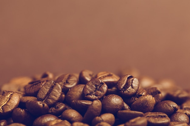 Bruine geroosterde koffiebonen op donkere achtergrond. espressodroog, aroma, zwarte cafeïnedrank. kopie ruimte