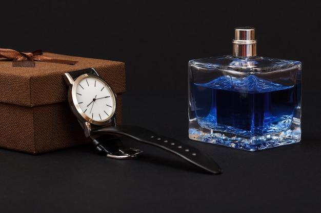 Bruine geschenkdoos, horloge met een zwarte leren band en parfums voor mannen op zwarte achtergrond. accessoires voor heren.