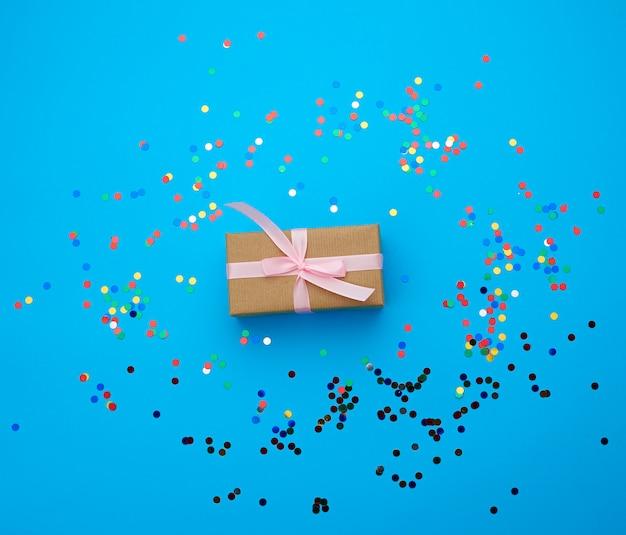 Bruine geschenkdoos verpakt in papier en gebonden met zijden lint op een blauwe achtergrond met veelkleurige glanzende confetti