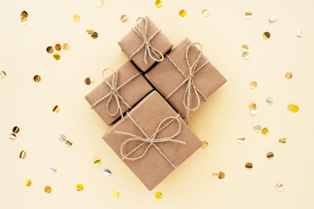 Bruine geschenken gemaakt van kraftpapier op een beige achtergrond en confetti, bovenaanzicht, plat gelegd. kleurtrend 2021, zeil champagne. moderne geschenkverpakkingen in natuurlijke tinten.