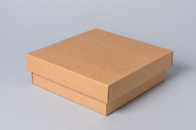Bruine gesloten kartonnen geschenkdoos met deksel op grijze achtergrond