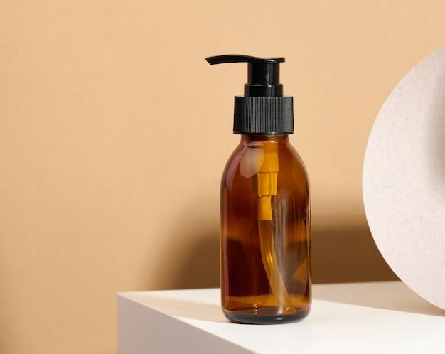 Bruine glazen fles met zwarte pomp van cosmetische producten op witte tafel. natuurlijke biologische spa cosmetica, beauty concept. mockup