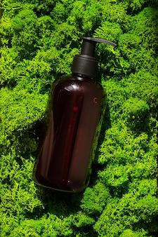 Bruine glazen fles op groene mos achtergrond in de ochtend stralen van licht eco cosmetische crème serum voor huid gezicht en lichaam concept van huidverzorging spa en wellness centrum natuurlijke schoonheidsproducten