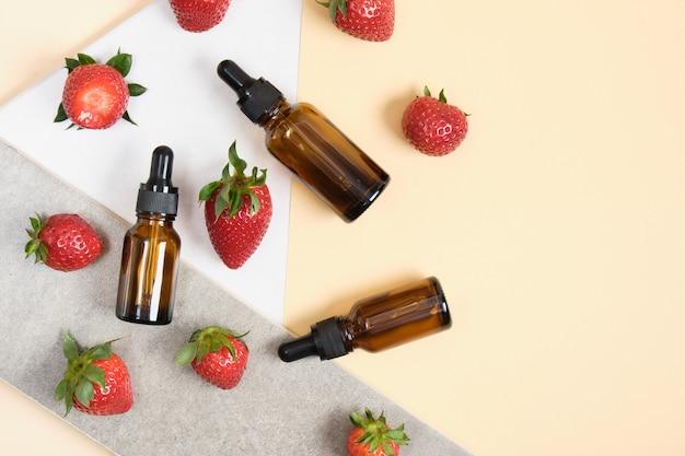 Bruine glazen flessen met pipet en aardbeien op beige, witte en grijze achtergrond, bovenaanzicht
