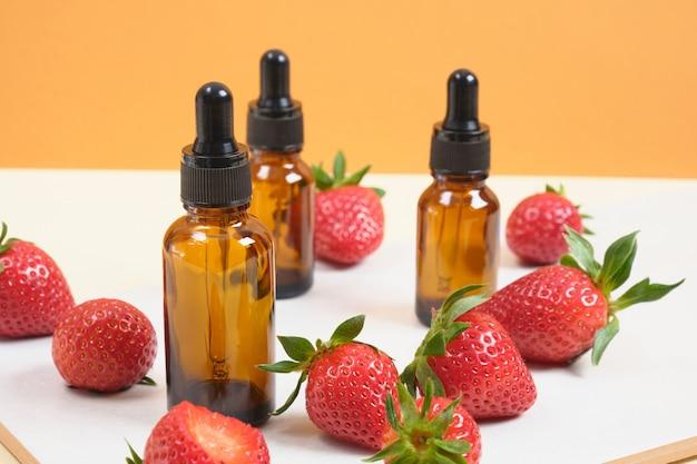 Bruine glazen flessen met pipet en aardbeien op witte en oranje achtergrond