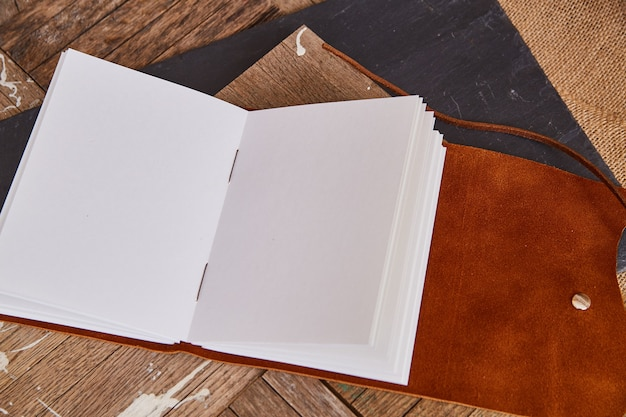 Bruine herten lederen omslag open blanco schetsboekpagina's op hout