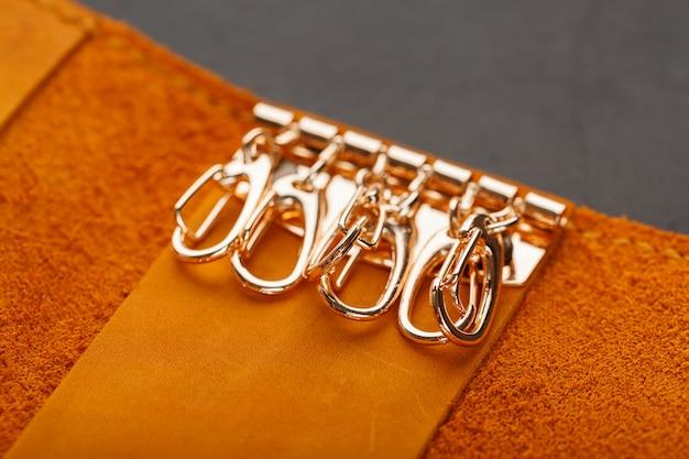 Bruine hoesportemonnee voor sleutels van echt nubuckleer op donker. met de hand gemaakte klinknagels en naadclose-up
