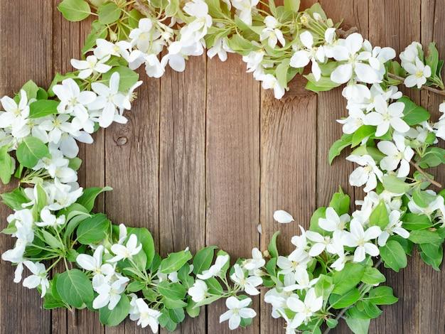 Bruine houten achtergrond. bloemen van appel aan de rand van het frame. plaats voor tekst