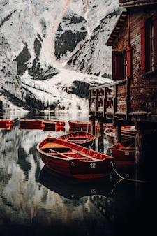 Bruine houten boot op water in de buurt van besneeuwde berg overdag